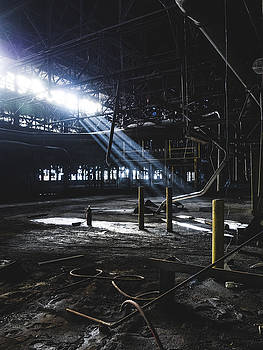 Light beams shining through abandoned building by Dylan Murphy
