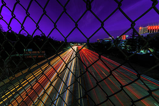 Light Trails of Vehicles on I-80 on A Summer Night In Downtown Reno Under a Purple Sky by Brian Ball