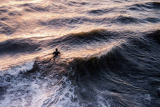 Lone surfer at sunset waiting for the next wave by Bradley Hebdon