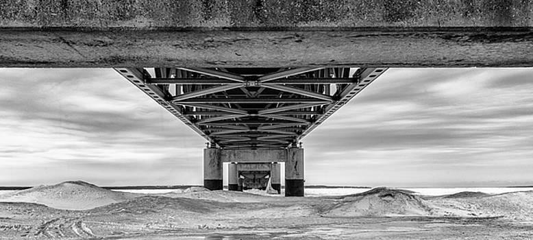 Mackinac Bridge in Winter Underneath  by John McGraw