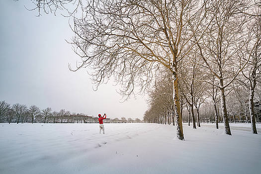 Man in red taking picture of snowy field and trees by William Lee