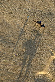 Sami Sarkis - Man leading two camels with tourists at sunset