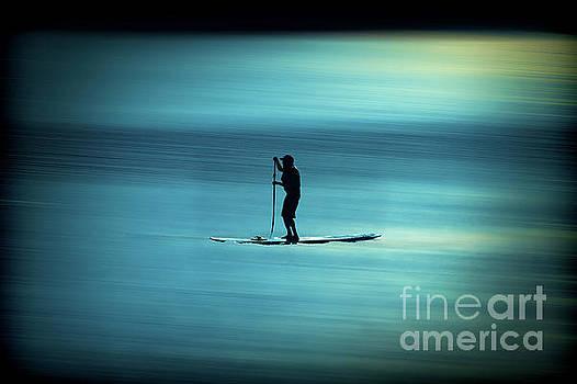 Dan Friend - man paddling board on lake sun setting