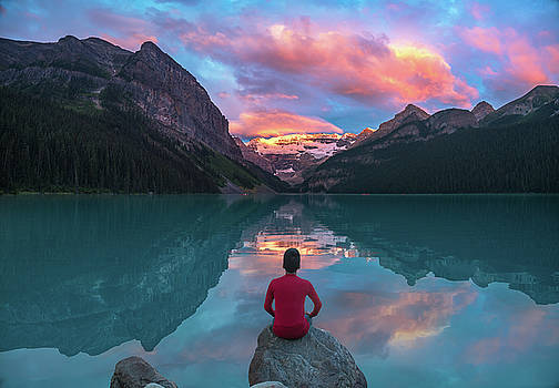Man sit on rock watching Lake Louise morning clouds with reflect by William Lee