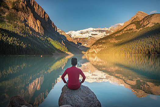 Man sit on rock watching Lake Louise reflections by William Freebilly photography