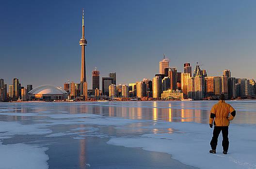 Reimar Gaertner - Man standing on frozen Lake Ontario ice looking at Toronto city