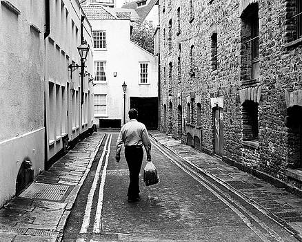Jacek Wojnarowski - Man Walking With Shopping Bag Down Narrow English Street