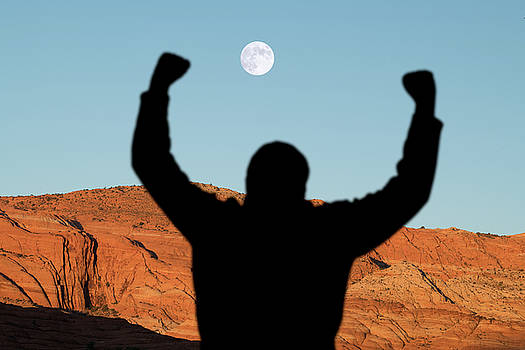 Man With Raised Arms In Desert Canyon by Steve Gadomski