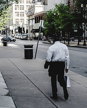 Man with shopping bag. St. Louis street photography. by Dylan Murphy