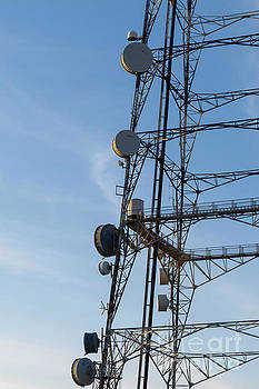 Microwave dish antenna on tower at sunrise by Carl Chapman