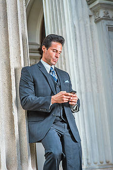 Alexander Image - Middle Age American Businessman texting on cell phone outside of