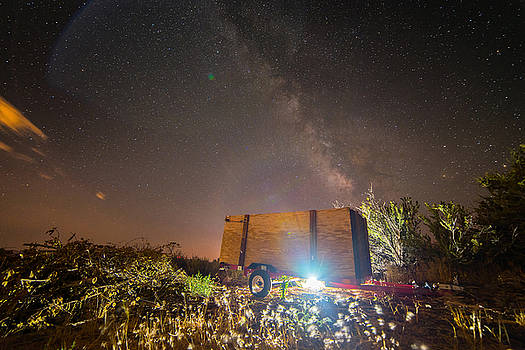Milky Way Over Trailer in Rural Setting Illuminated by Light Underneath During Summer by Brian Ball