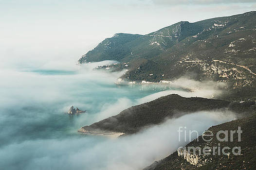 Misty ocean by the mountains by Ines Leonardo