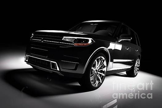 Michal Bednarek - Modern black SUV car in a spotlight on a black background.