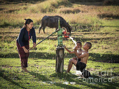 Mother her sons shower outdoor from Groundwater pump. by Tosporn Preede