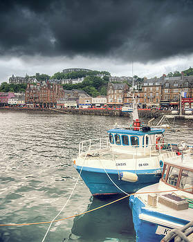Oban Harbour under a dark sky by Ray Devlin