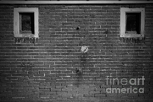 Old brick wall background with 2 windows in black and white. by Paul Koomen