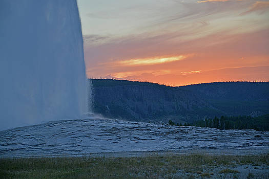 Old Faithful Geyser Erupting at Sunset by Bruce Gourley