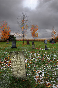 Reimar Gaertner - Old gravestone for children lit by break in clouds on a cold aut