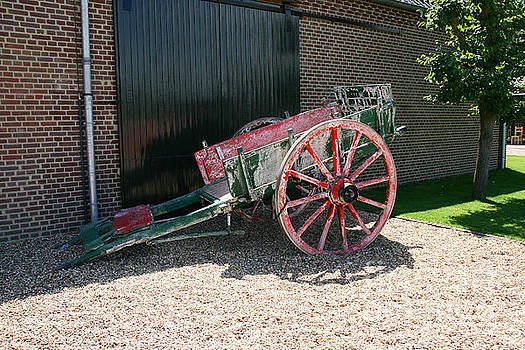 Old green and red horse wagon in front of a barn. by Paul Koomen