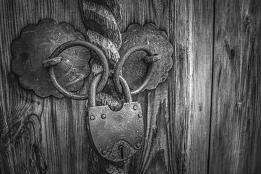 Old padlock on a wooden door by Julian Popov