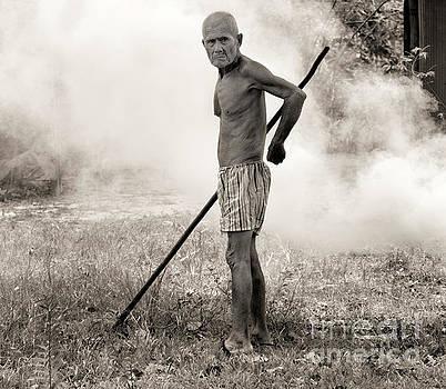 Chuck Kuhn - Older Cambodian Male Burning Leaves