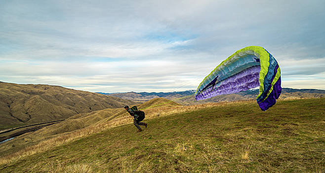 Paraglider launching his wing on a hill near Horseshoe Bend, Ida by Elijah Weber