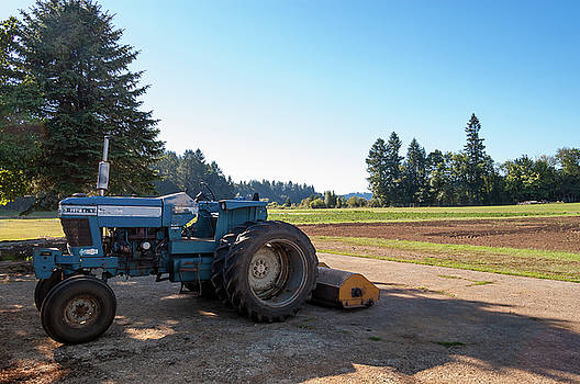 Parked farm tractor in shade after plowing field by Bradley Hebdon