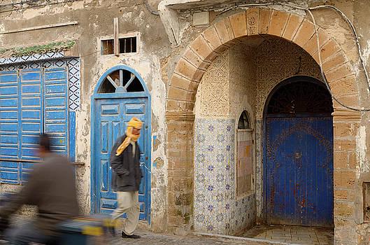 Reimar Gaertner - Passersby and blue doors in Essaouira Medina with ornate stonewo