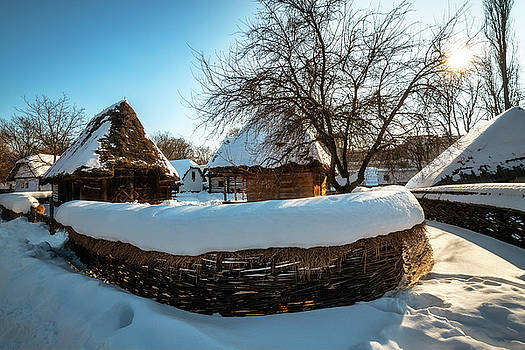 Pastoral landscape with traditional old cottages in winter by Daniela Constantinescu