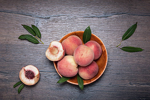 Peaches on a dark wooden background by Sergei Dolgov
