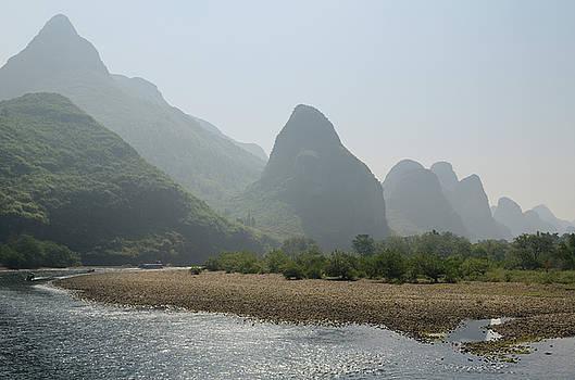 Reimar Gaertner - Pebble shore of the Li River with limestone Karst peaks receding