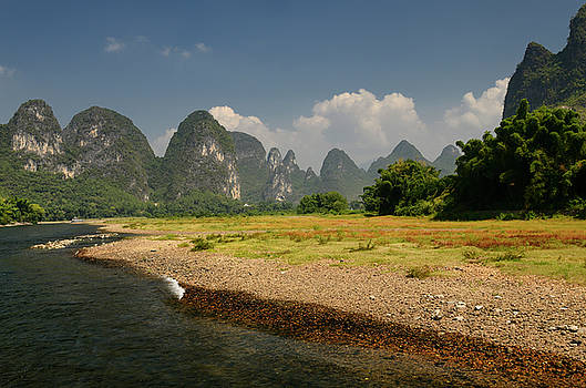 Reimar Gaertner - Pebble shore of the Lijiang River China with pointed Karst cones