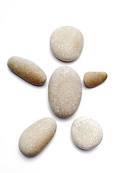 Sami Sarkis - Pebbles arranged in shape of human on white background