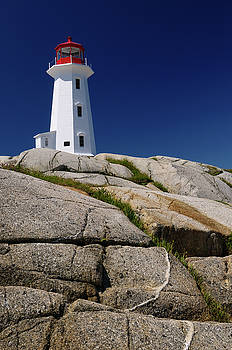 Reimar Gaertner - Peggys Cove lighthouse on smooth granite rocks against a blue sk