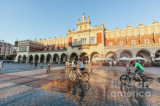 Michal Bednarek - People cycling on the main market square of Cracow, Poland