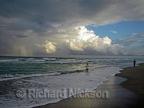 People on the beach as storm approaches by Richard Nickson