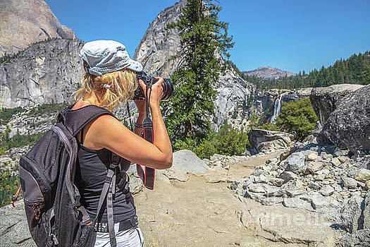 Photographer in Yosemite waterfalls by Benny Marty
