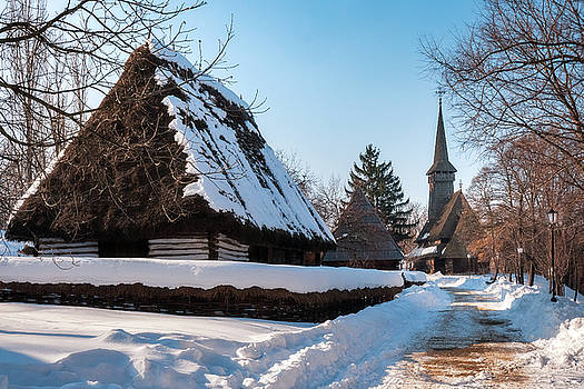 Picturesque street covered in snow at the Village Museum in Bucharest by Daniela Constantinescu
