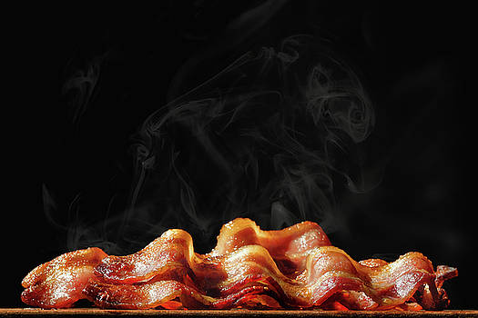 Pile of Sizzling Bacon Isolated on Black by Susan Schmitz