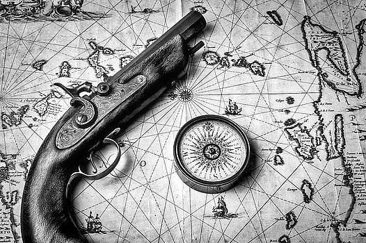 Pistole And Compass On Old Map In Black And White by Garry Gay