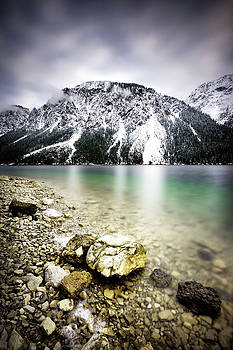 Plansee lake and Alps mountains during winter, snowy view, Tyrol, Austria. by Marek Kijevsky