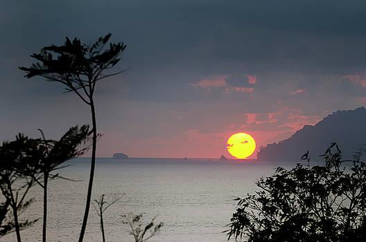 Reimar Gaertner - Red ball tropical sun setting below the Pacific Ocean horizon at