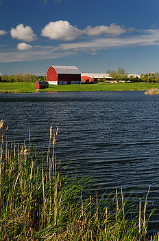 Reimar Gaertner - Red barn on blue lake in Lincolnville Ontario with green grass c