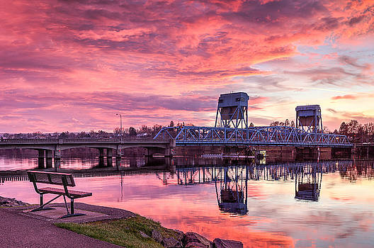 Red Clouds Blue Bridge and a Bench by Brad Stinson