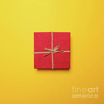Red gift box with rope bow on yellow background - Flat lay by Aleksandar Mijatovic