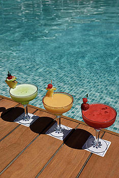 Reimar Gaertner - Red yellow and green cocktails on a wooden deck next to a pool