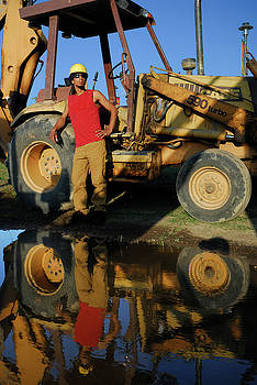 Reimar Gaertner - Reflection of a construction worker and backhoe in a puddle
