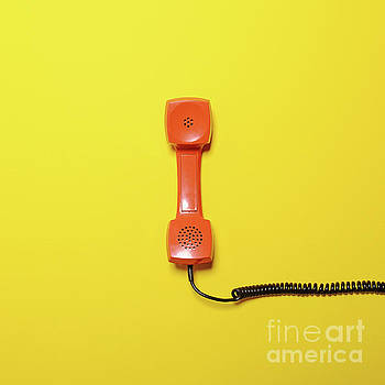 Retro orange telephone tube on yellow background - Flat lay by Aleksandar Mijatovic