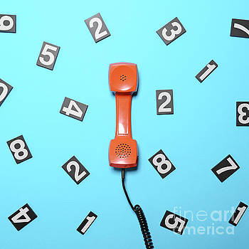Retro orange telephone tube with numbers around it on blue backg by Aleksandar Mijatovic